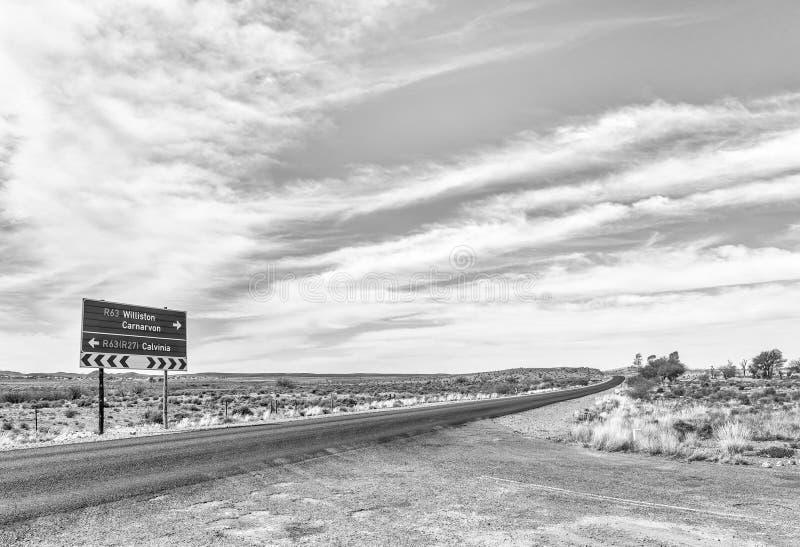 Sinal de estrada direcional na estrada R63 perto de Williston monocromático imagem de stock