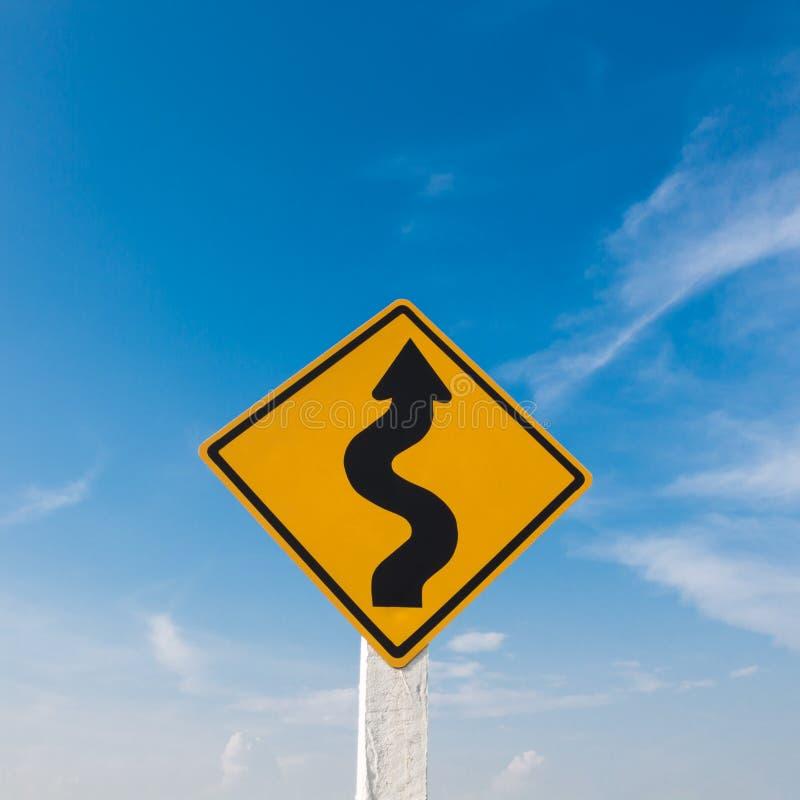 Sinal de estrada do enrolamento com um céu azul imagem de stock
