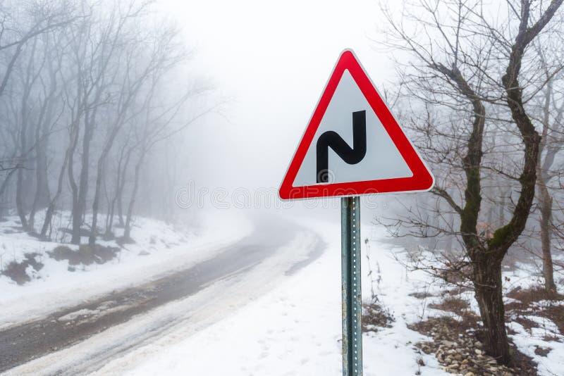 Sinal de estrada na estrada na floresta do inverno foto de stock royalty free