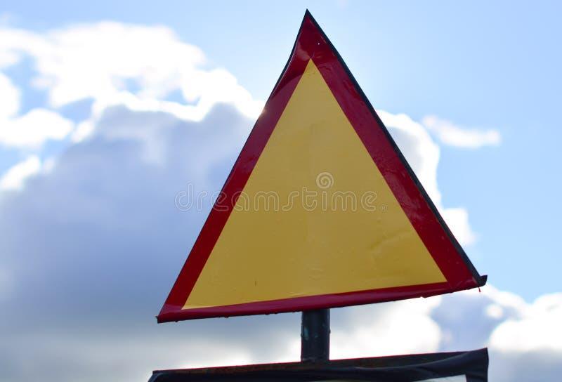 Sinal de estrada triangular em um fundo do céu fotos de stock