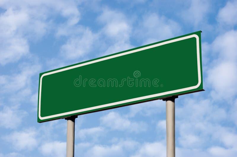 Sinal de estrada verde em branco de encontro ao céu claro de Cloudscape imagens de stock