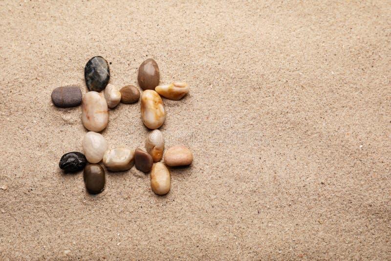 Sinal de Hashtag feito de pedras decorativas na areia imagens de stock royalty free