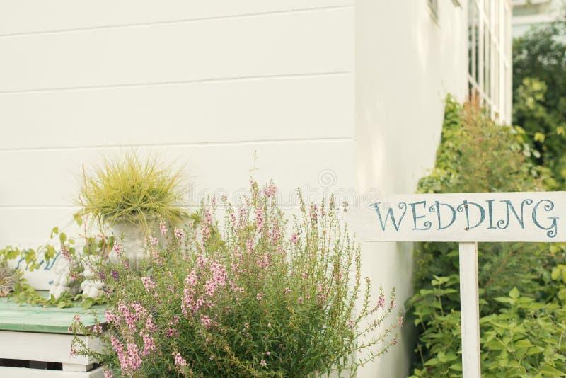 Sinal de madeira do casamento contra o fundo verde do borrão Quadro indicador de madeira com a inscrição no casamento branco da p imagem de stock
