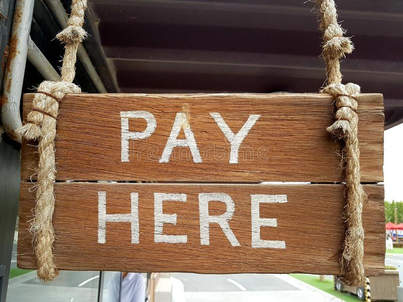 Sinal de madeira do vintage indicar o lugar do caixa Pagamento escrito aqui em pranchas foto de stock royalty free