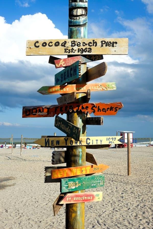 Sinal de madeira na praia do cacau, florida, EUA que apontam aos lotes do dif fotos de stock
