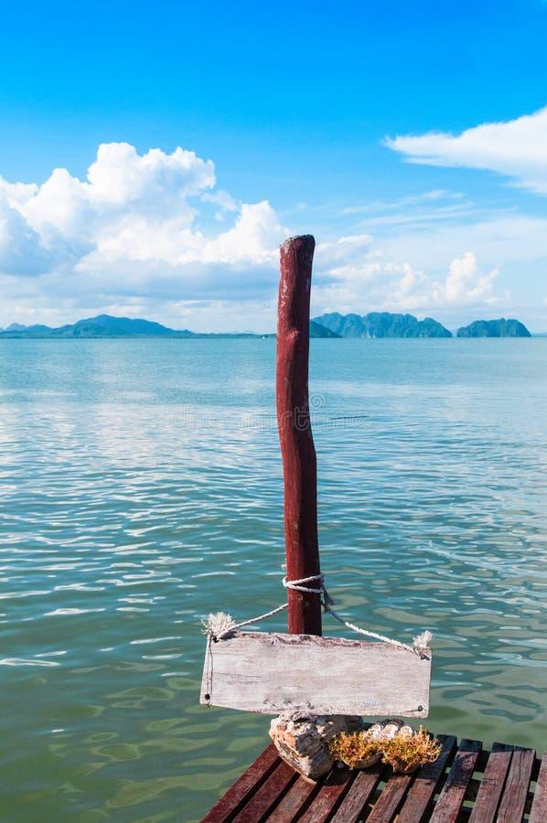 Sinal de madeira que pendura no polo de madeira pelo mar com céu azul e foto de stock