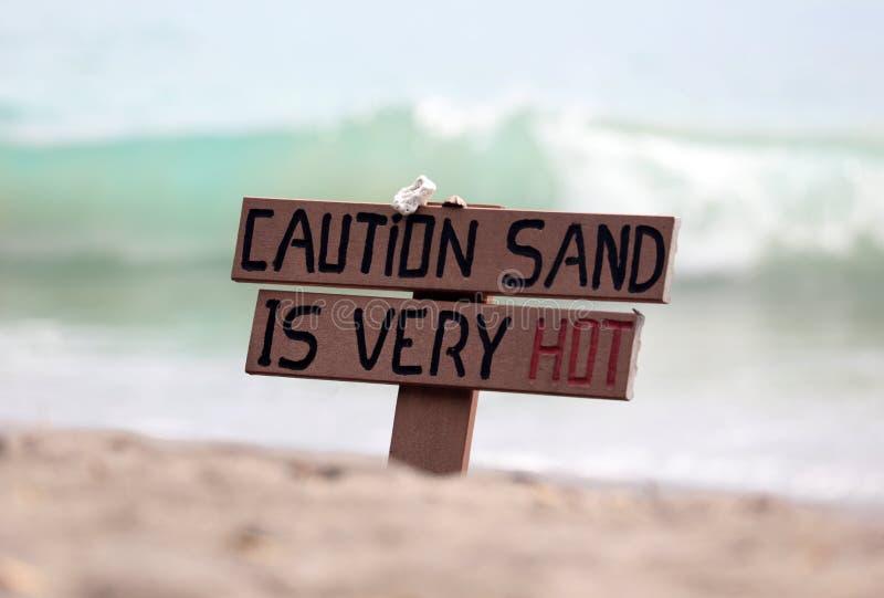 Sinal de madeira quente do cuidado na praia com as ondas da areia e de oceano fotos de stock