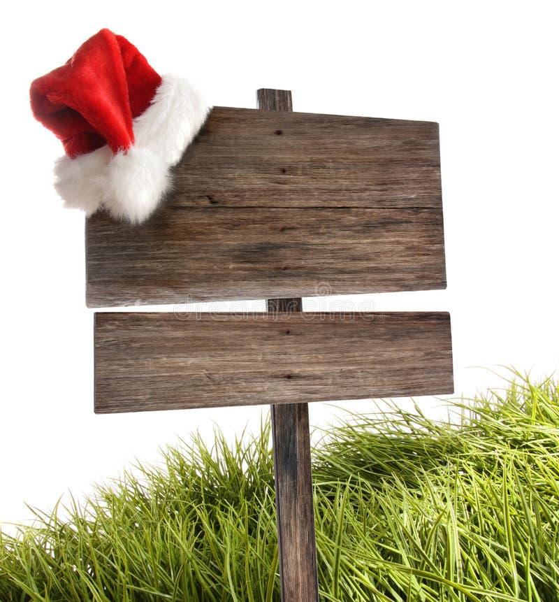 Sinal de madeira resistido com o chapéu de Santa no branco foto de stock