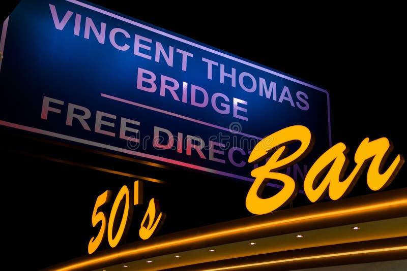 Sinal de néon amarelo com a inscrição da barra dos anos 50 no fundo do sinal de estrada Vincent Thomas Bridge livre fotos de stock royalty free