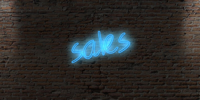 sinal de néon da letra com as vendas da palavra em uma parede da obscuridade do tijolo imagem de stock royalty free