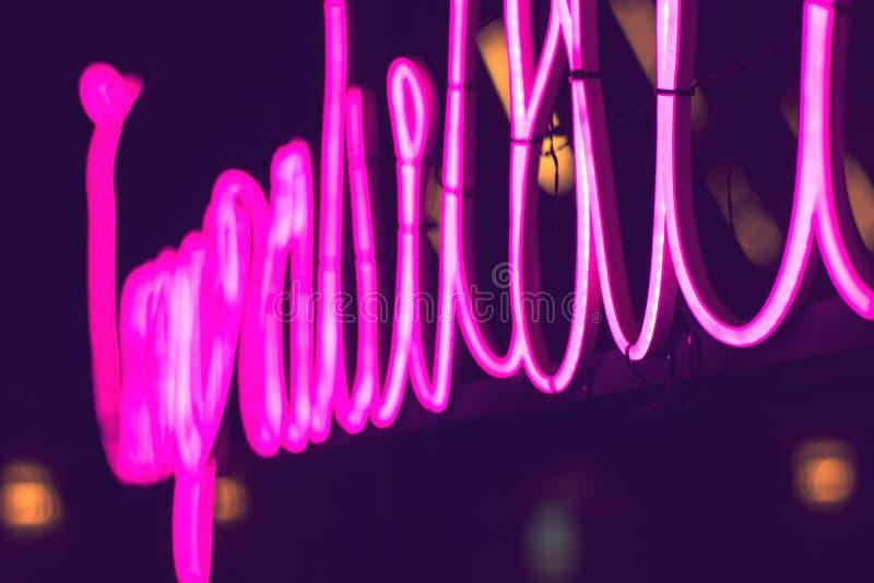 Sinal de néon do rosa do sumário com fundo borrado da luz do tubo de néon fotografia de stock