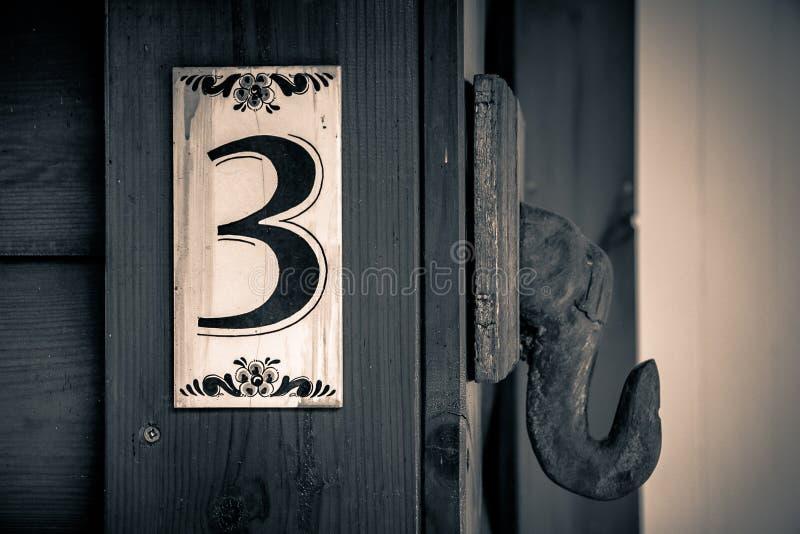 Sinal de número velho do apartamento na parede da madeira com o número três nele imagem de stock royalty free