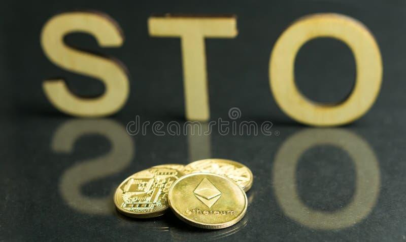 Sinal de oferecimento simbólico da segurança STO com letras e as moedas de ouro de madeira na frente dele, conceito de Ethereum fotografia de stock