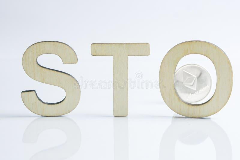 Sinal de oferecimento simbólico da segurança STO com letras de madeira e a moeda de prata de Ethereum atrás, conceito de Ethereum imagens de stock royalty free