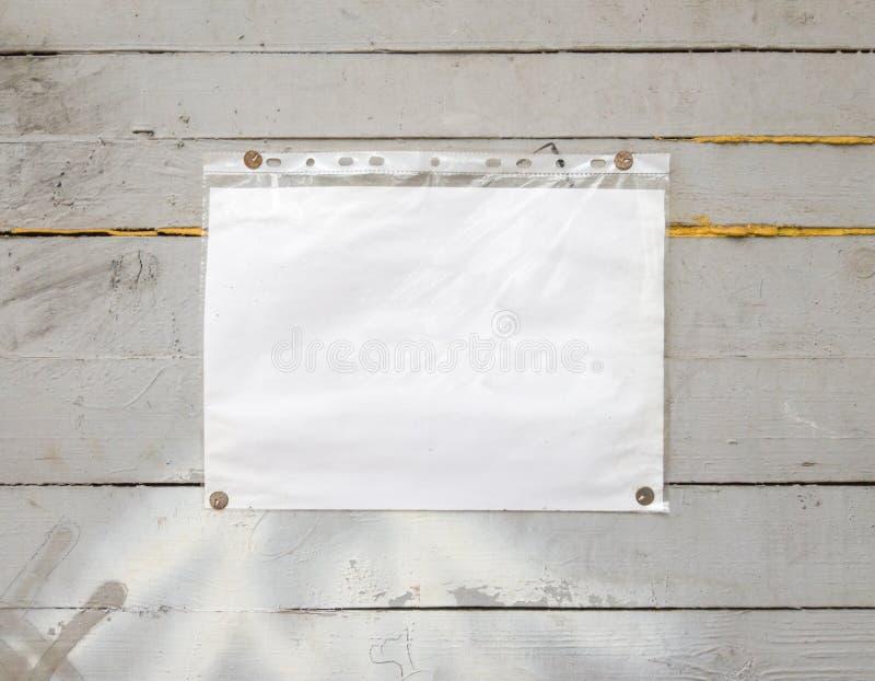 Sinal de papel branco com rebites, fundo vintage sobre um fundo de madeira cinza Parede texturizada de madeira, pesa um branco br fotografia de stock royalty free