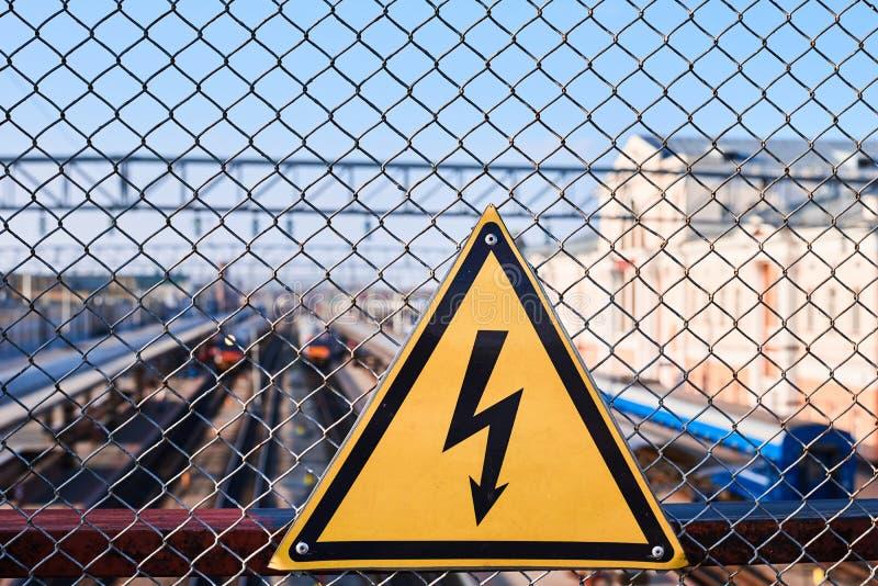 Sinal de perigo elétrico Relâmpago no fim amarelo do fundo acima Eletricidade de alta tensão em uma estação de trem imagens de stock royalty free
