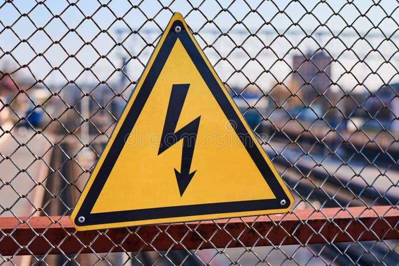 Sinal de perigo el?trico Rel?mpago no fim amarelo do fundo acima Eletricidade de alta tens?o em uma esta??o de trem imagens de stock royalty free