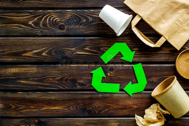 Sinal de reciclagem verde com materiais de desperdício, copos, saco de papel para o copyspace de madeira da opinião superior do f fotos de stock