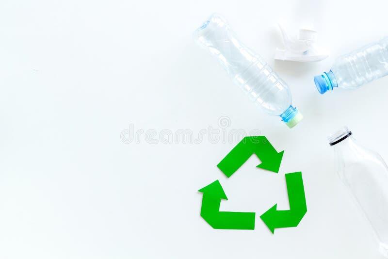 Sinal de reciclagem verde com materiais de desperdício, garrafas para o conceito de salvaguarda da ecologia no copyspace branco d foto de stock royalty free