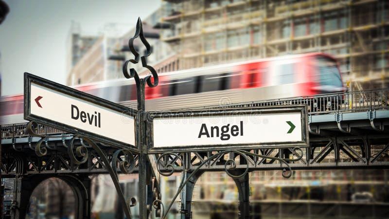 Sinal de rua ao anjo contra o diabo foto de stock royalty free