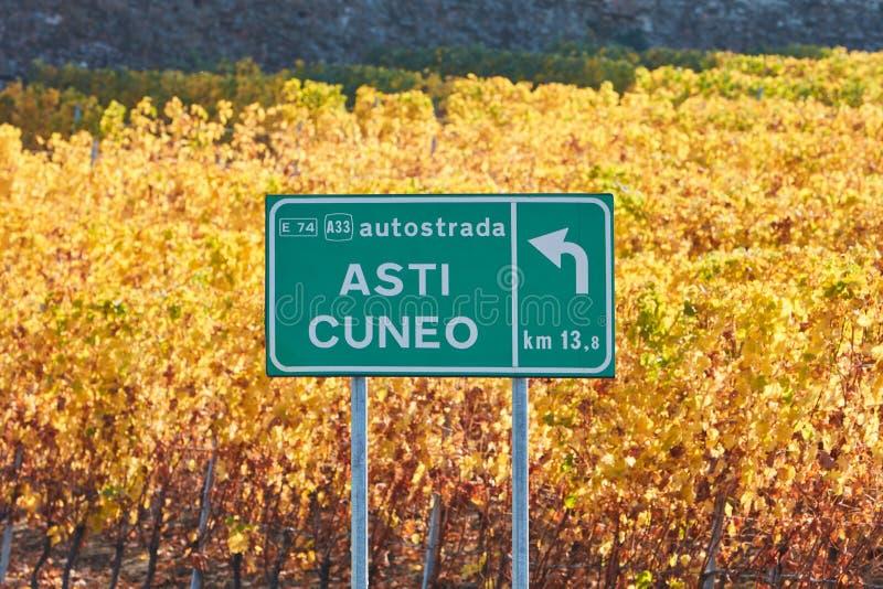 Sinal de rua da estrada de Asti Cuneo e vinhedo no outono em Itália imagens de stock royalty free