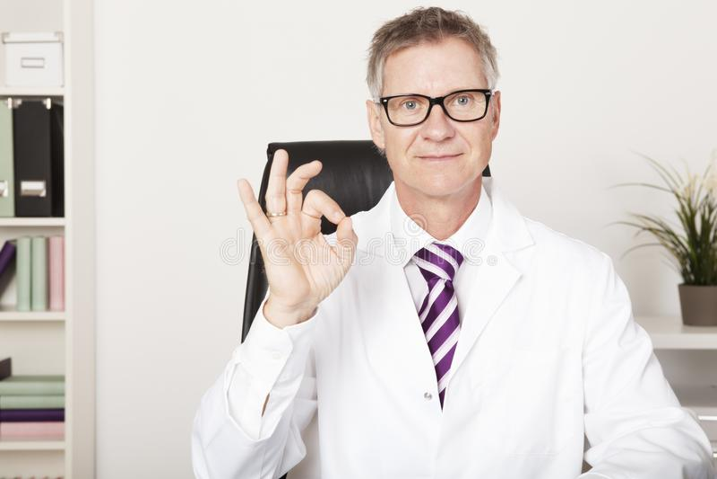 Sinal de sorriso do doutor Showing Okay Hand fotos de stock royalty free