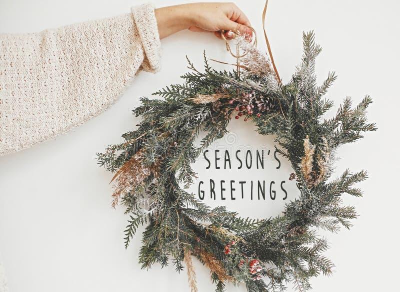 Sinal de texto de saudações da temporada no natal rustic wreath na mão da menina Pavimento rural criativo com ramos de abeto, bag foto de stock