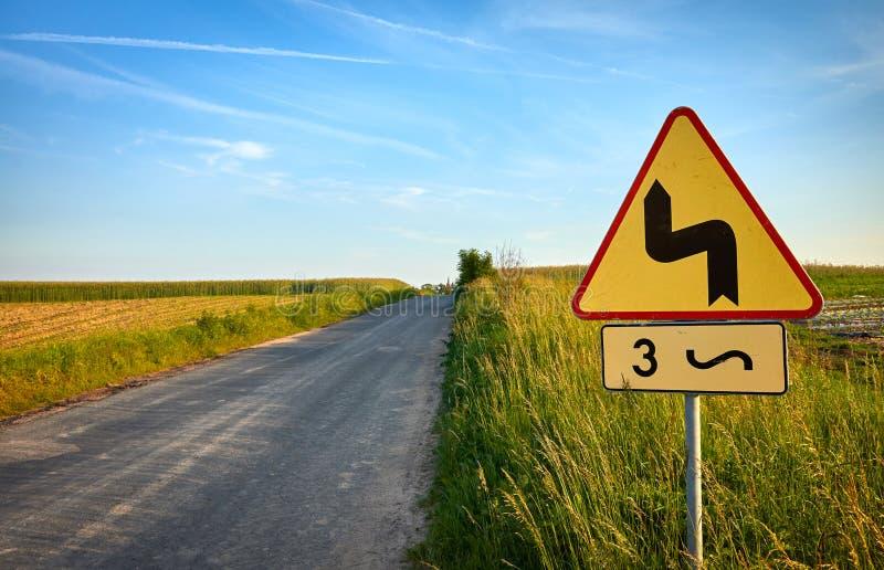 Sinal de tráfego perigoso das curvaturas por uma estrada secundária no por do sol fotografia de stock