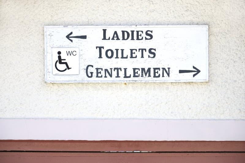 Sinal deficiente do wc dos toaletes dos cavalheiros das senhoras no fundo liso da parede imagens de stock royalty free