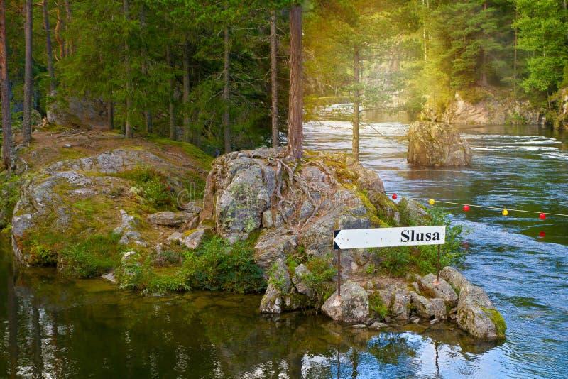 Sinal direcional da derrota, seta na floresta no banco de rio Vista do canal de Telemark com fechamentos velhos fotos de stock