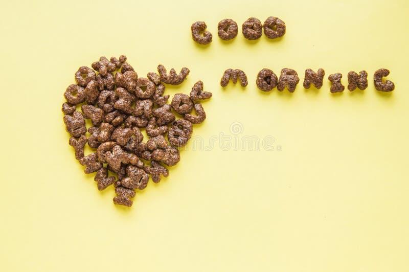 Sinal do coração na tabela e no bom dia da inscrição, feitos do café da manhã seco - flocos do chocolate no formulário das letras fotos de stock
