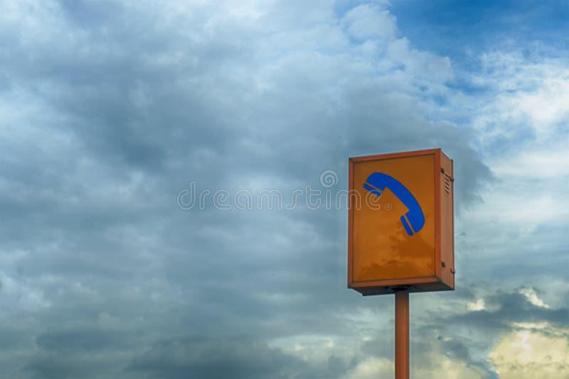 Sinal do fundo do telefone da emergência e do céu azul fotografia de stock royalty free