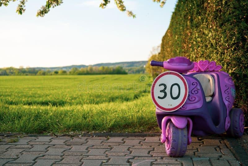 Sinal do limite de velocidade de 30 sob a forma de um passeio das crianças cor-de-rosa no veículo fotos de stock royalty free