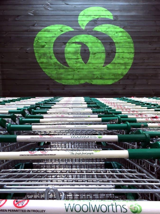 Sinal do logotipo dos supermercados de Woolworths com troles da compra fotografia de stock