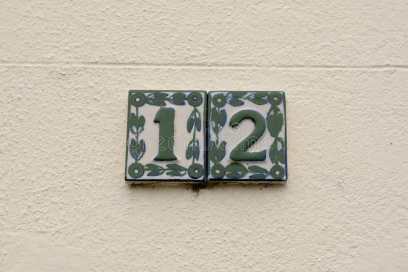 Sinal do número da casa 12 na parede - nos azulejos fotografia de stock