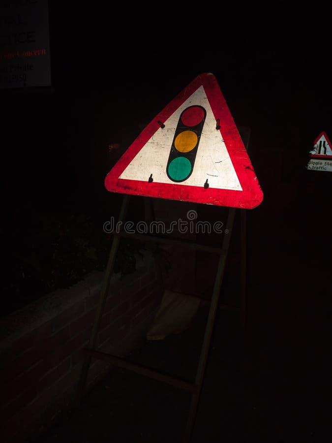 sinal do sinal no constructio verde ambarino vermelho do triângulo da noite fotografia de stock