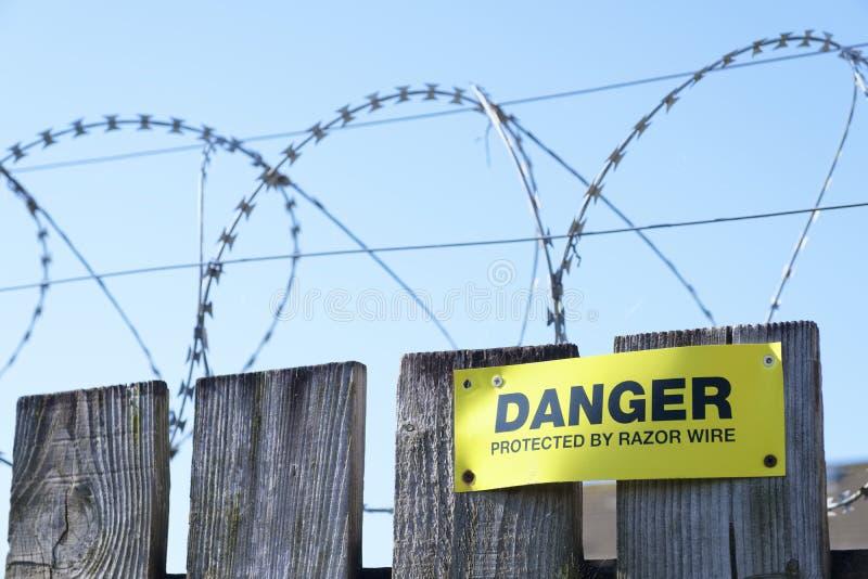 Sinal do perigo da segurança da proteção da cerca de fio da lâmina no terreno de construção da construção da cerca fotografia de stock