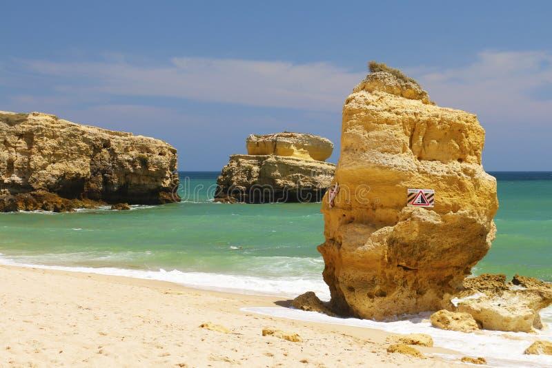 Sinal do perigo na rocha na praia fotos de stock royalty free