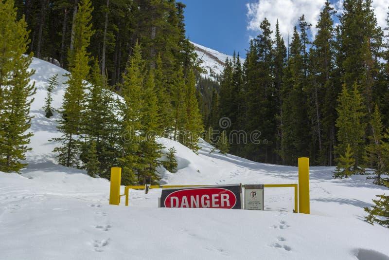 Sinal do perigo que obstrui uma estrada em um Snowbank em uma floresta da montanha foto de stock