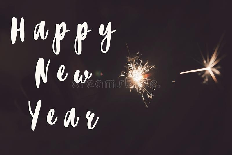 Sinal do texto do ano novo feliz, ano novo feliz e conceito do Feliz Natal mão que guarda a queimadura imagens de stock
