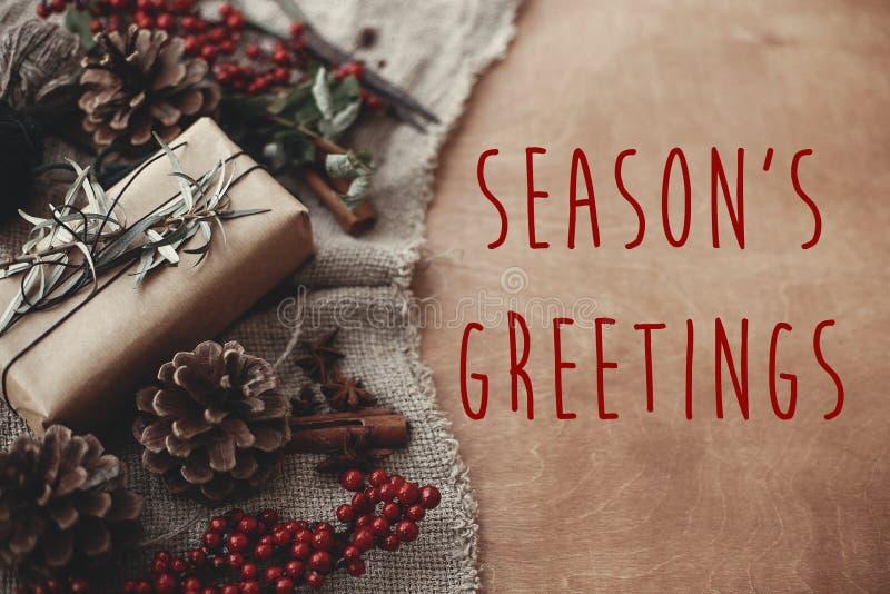 Sinal do texto dos cumprimentos da estação na caixa de presente rústica à moda do Natal com ramos do abeto, bagas vermelhas, cone foto de stock royalty free