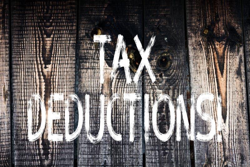 Sinal do texto que mostra deduções fiscais A redução conceptual da foto no dinheiro das economias do investimento dos impostos re fotos de stock