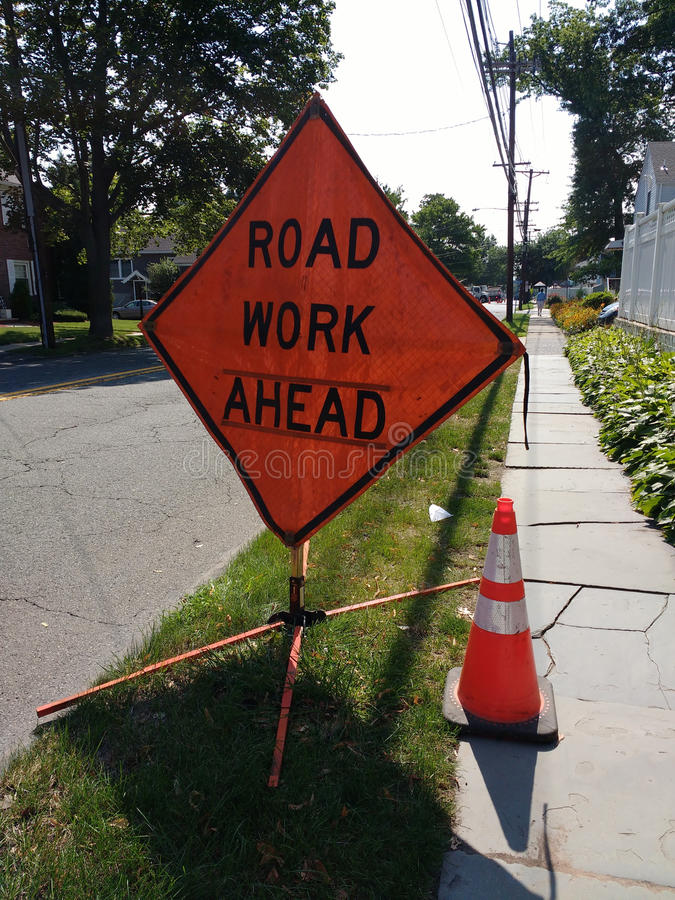 Sinal do trabalho de estrada adiante com o cone reflexivo alaranjado da segurança de tráfego foto de stock royalty free