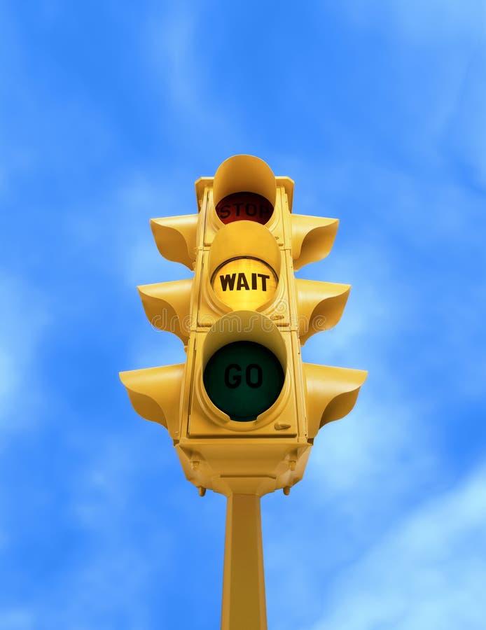 Sinal do vintage com luz amarela da ESPERA no fundo do céu azul foto de stock royalty free