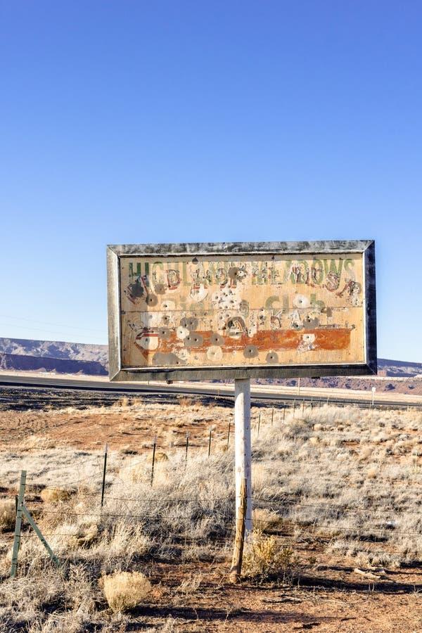 Sinal do vintage dos prados velhos que montam o clube usado como a pr?tica de alvo em Route 66 velho, New mexico imagens de stock royalty free