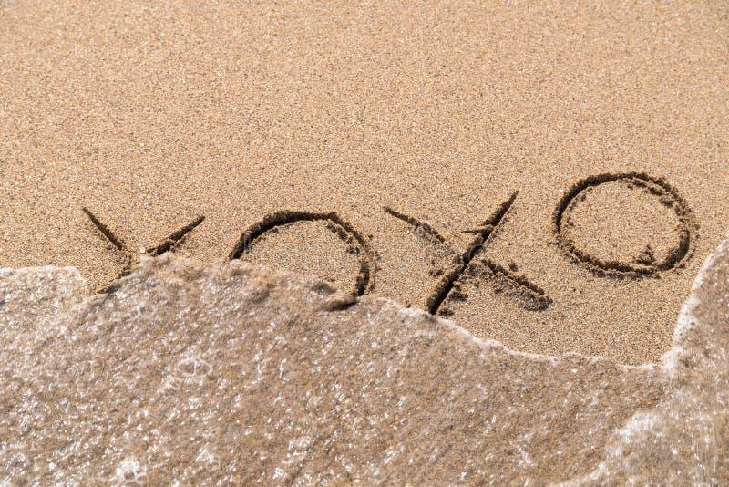 Sinal dos abraços e dos beijos XOXO na areia imagens de stock royalty free