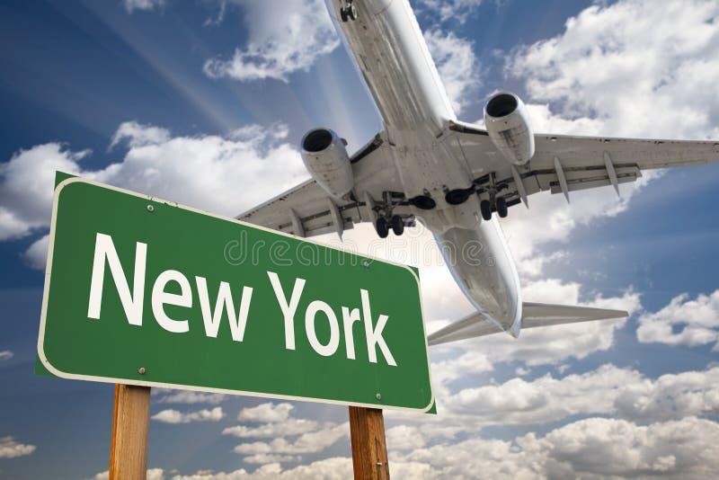 Sinal e avião de estrada do verde de New York acima foto de stock royalty free