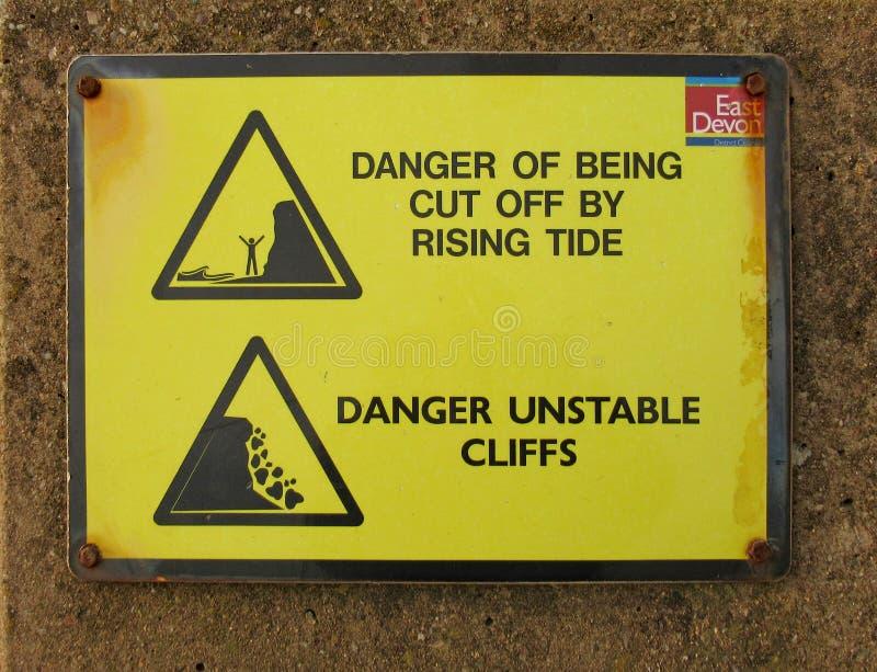 Sinal em dizer da parte dianteira de mar de Sidmouth dos perigos dos aumentos e de penhascos de queda imagem de stock royalty free