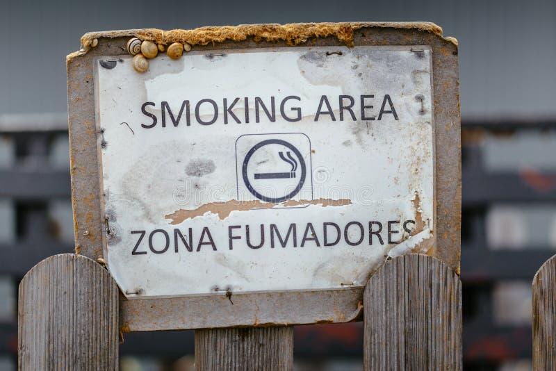 Sinal envelhecido da área de fumo com os caracóis colados fotografia de stock