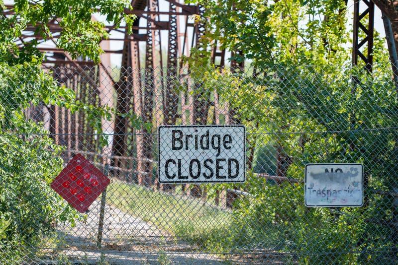 Sinal fechado da ponte na frente da ponte dilapidada com overgrowth das árvores e dos arbustos imagem de stock royalty free
